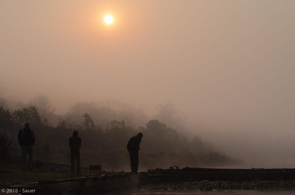 Männer und Flöße im Nebel bei Sonnenaufgang