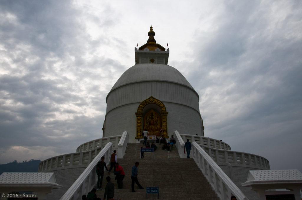 World Peace Stupa in Pokhara mit den vier goldenen Buddha-Statuen, die je in eine Himmelsrichtung blicken.