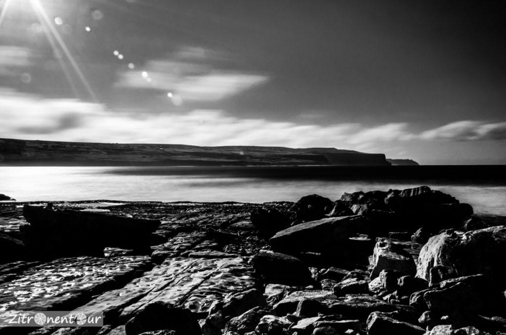 Langzeitbelichtung der wilden Felsenküste in Doolin. Im Hintergrund die Cliffs of Moher