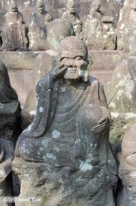 Statue eines in der Nase bohrenden Buddha im Garten Gohyaku Rakan