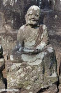 Statue eines lächelnden Buddha im Garten Gohyaku Rakan